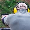 Man shooting from 9mm Glock in outdoor shooting range